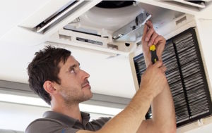 Man Servicing Ceiling Cassette Air Con